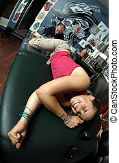 Tattoo pain - A tattoo artist applying his craft onto the...