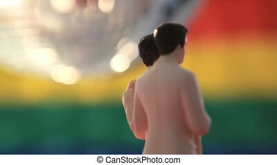 Gay groom cake toppers revolving with disco ball in front of...