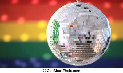 Shiny disco ball revolving against rainbow flag background