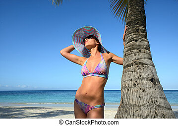 Woman in summer hat sunbathing under a palm tree on a...