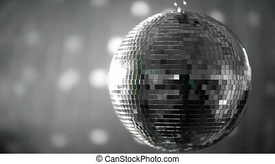Shiny disco ball revolving on grey background