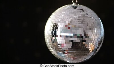 Shiny disco ball revolving on black background