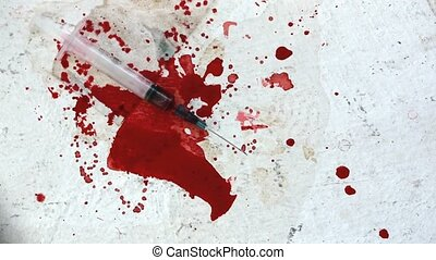 Syringes falling on bloody surface - Syringes falling on...