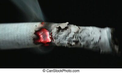 Burning cigarette with ash on black background