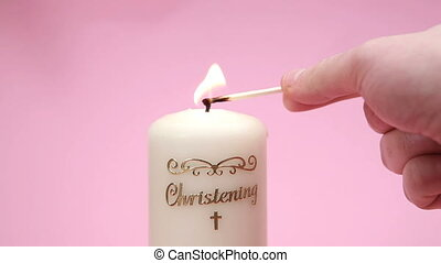 Christening candle being lit on pink background