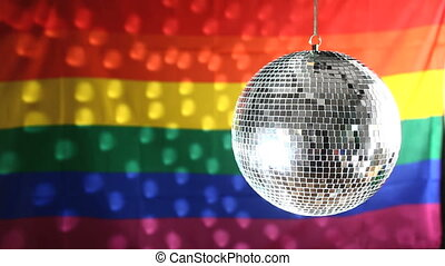 Disco ball revolving against gay pride flag with light...