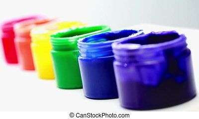 Rainbow paint pots in a row for gay pride on white...