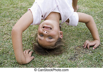 girl doing cartwheel in the grass - young girl doing...