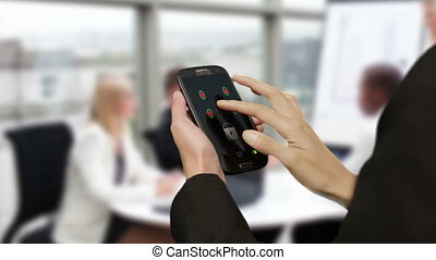 Businesswoman using smart phone in meeting to view graph and...