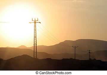 Power lines and array of electric pylons in Judea desert