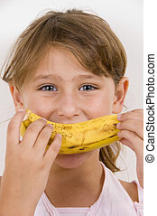 little girl eating banana and looking at the camera