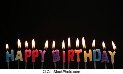 Happy birthday candles being blown out on black background