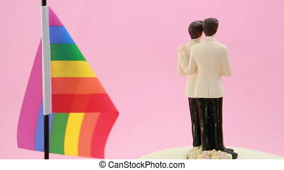 Gay groom cake toppers in front of rainbow flag revolving on...