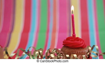 Candle on birthday cupcake blown out on rainbow background