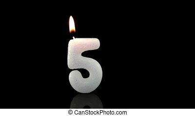 Fifth birthday candle on black background