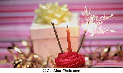 Sparklers on a birthday cupcake with gift on pink striped...