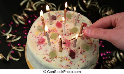 Hand lighting candles on birthday c