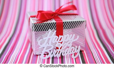 Focus on birthday gift on pink striped background