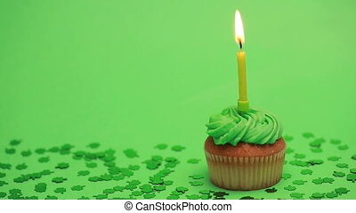 St patricks day cupcake with shamrock confetti burning...