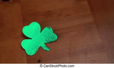 Hand putting down empty pint beside large shamrock on wooden...