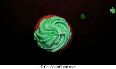 St patricks day cupcake revolving with green shamrock...