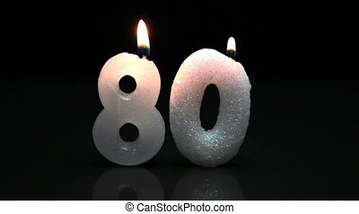 Eightieth birthday candles on black surface