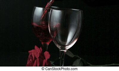 Two glasses of red wine being poured with red rose on black...