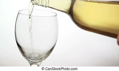 Glass being filled with white wine on white background
