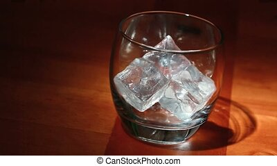 Tumbler of ice being filled with whiskey on wooden surface