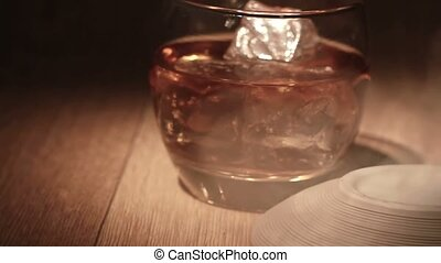 Cigar being placed beside tumbler of whiskey on the rocks on...