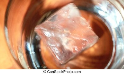 Overhead of ice and whiskey filling tumbler glass close up