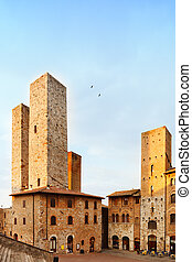 San Gimignano landmark medieval town. Sunset on towers in central Erbe Square. Tuscany, Italy, Europe.