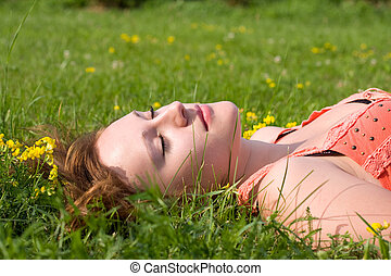 beautiful girl relaxing on the green grass