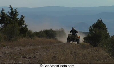 ATV passes camera with mountains and distance