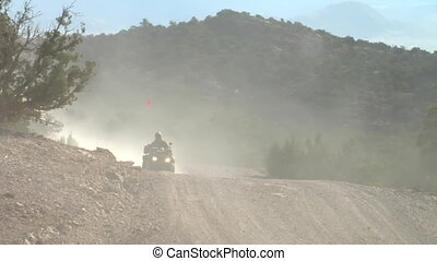 four wheeler with headlights on dusty road