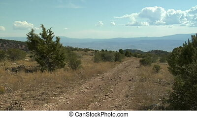 multiple ATVs pass camera with mountains in distance
