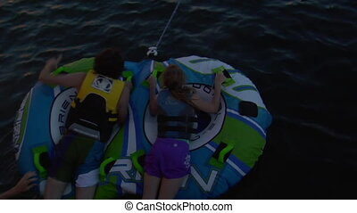 kids on inter-tubes pulled by ski boat