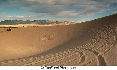 two ATV riders Circle large sand dune