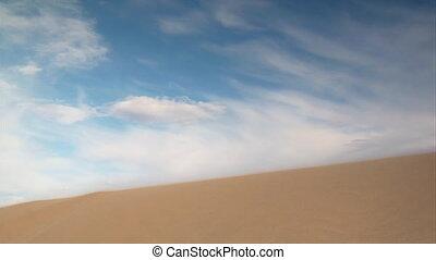 ATV rider jumps sand dune slow-motion
