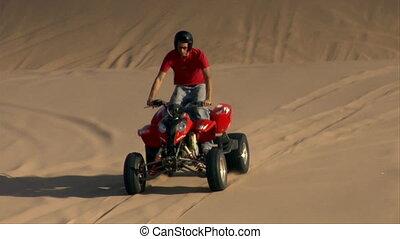ATV riders frolic and jump on sand dunes