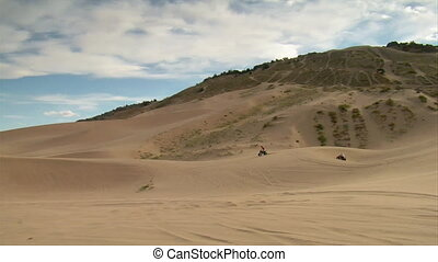 ATV riders on wide desert landscape