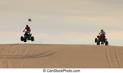 ATV riders come over sand dune and past camera