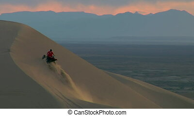 ATV riders scales steep sand dune with mountains and distance