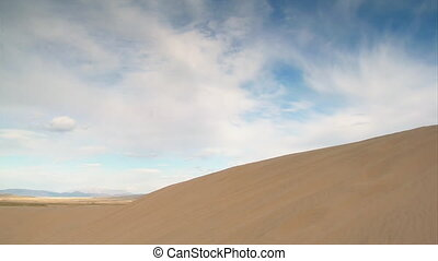 ATV rider jump sand dune in slow motion with nice clouds