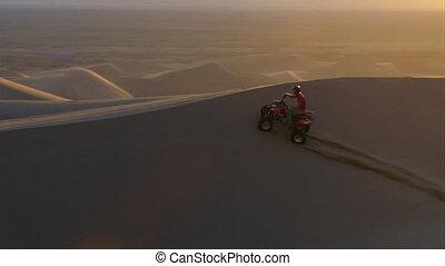 ATV rider on dunes at sunset