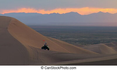 ATV rider on sand dune and gorgeous mountain sunset