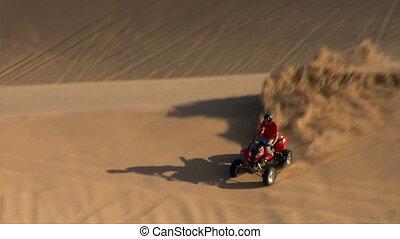 slow-motion ATV rider kicks up sand