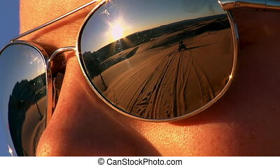 ATV riders on sand dunes reflected in sunglasses