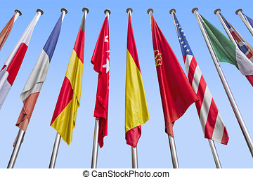 International flags in a row against a blue sky. Clipping...