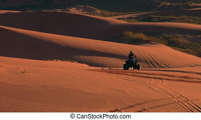 pull back from ATV riders to wide Vista of desert sand dunes